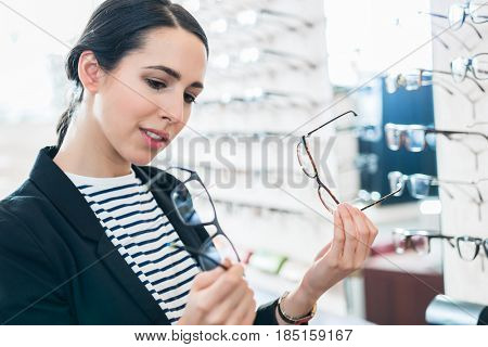 Woman comparing glasses at optician store