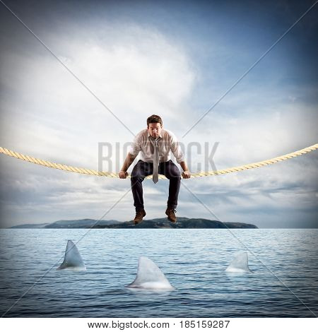 Man sitting on a rope over the sea with sharks. Concept of difficult and risk in business affairs
