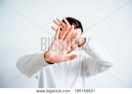 Man is covering his face with his hand
