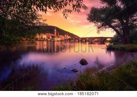 Heidelberg Germany dreamy sunset colors over the Neckar river with the Old Town and Bridge framed by silhouettes of trees