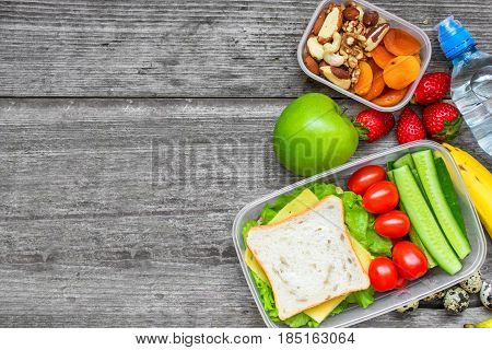Healthy lunch boxes with sandwich, eggs and fresh vegetables, bottle of water, nuts and fruits on rustic wooden background. top view with copy space