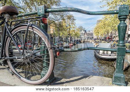 Back wheel of a holland bike standing on bridge in the streets of AMsterdam, Netherland
