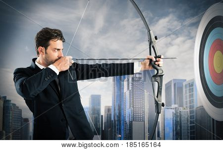 Businessman with bow and arrow aiming a target