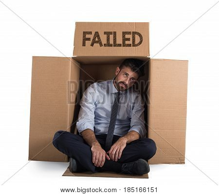 Desperate and failed businessman in a cardboard on the street