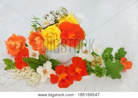 Medicinal flower and herb selection of nasturtium, rose, elderflower, ladies mantle, orange blossom, marjoram, mint and angelica seed heads used in natural herbal medicine.