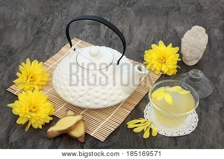 Chrysanthemum flower tea with oriental teapot, glass cup with lid and ginger spice. Also used  in traditional chinese herbal medicine.