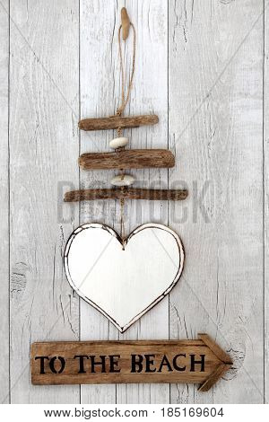 Rustic driftwood to the beach sign with with heart shaped mobile on distressed white wood background.