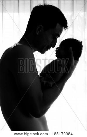 Father day bonding concept with newborn baby nursing. Father is playing and talking with newborn baby beside window. Single Dad concept