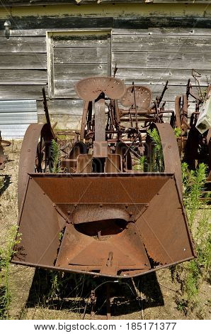 A very old and rusty horse drawn potato planter with a large rusty hopper