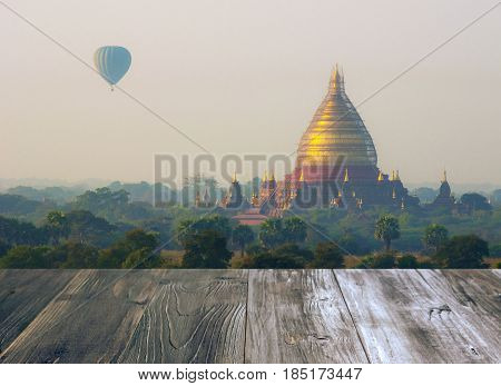 vintage wood terrace with view of hot air balloon over Temple in Bagan misty sunrise at morning Myanmar copy space color tone effect soft focus selective focus.