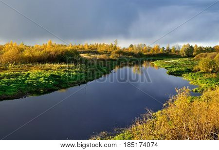 Autumn sunset landscape with river and yellowed trees. Autumn river in sunny weather. Autumn sunset landscape - river and yellowed autumn trees at autumn evening. Colorful autumn background