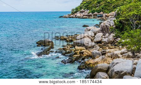 Costline of Koh Tao Islands in Thailand. Granite Rocks and blue clear water hitting Rocks. Thailand