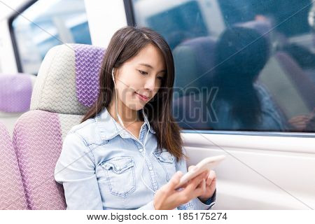 Woman taking express train and listen to music from mobile phone