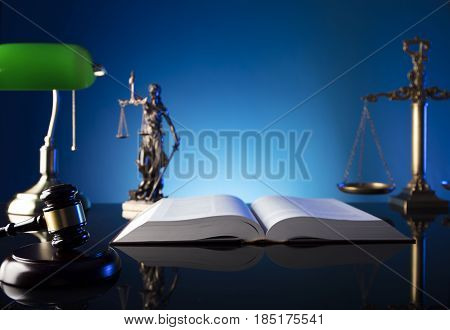 Lawyer, counselor office. Consultation with a lawyer concept.  Gavel of the jugde and scale of justice on old glass table and blue background.