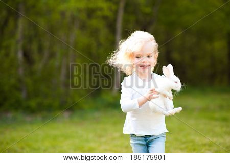 Laughing baby girl 3-4 year old holding small rabbit running in meadow. Looking at camera. Childhood.