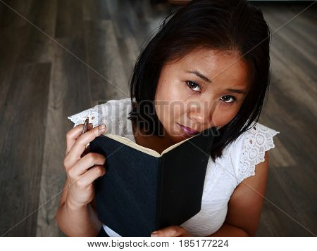 Woman Holding A Notebook And A Pen, Thinking