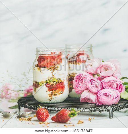 Healthy spring breakfast. Greek yogurt, granola, fresh strawberry breakfast in jars, pink raninkulus flowers, marble background, selective focus, copy space, square crop. Clean eating food concept