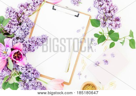 Freelancer or blogger workspace with clipboard, notebook, pen, lilac, tulips and accessories on white background. Flat lay, top view. Beauty blog concept.