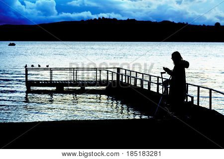 Silhouette young woman using mobile phone at Lake Taupo in the evening North Island of New Zealand