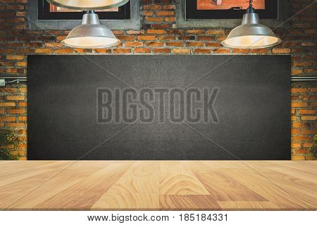 wood frame blackboard backgrounds with wood table top in the kitchen for product display menu board with lamp and light on wall in restaurant