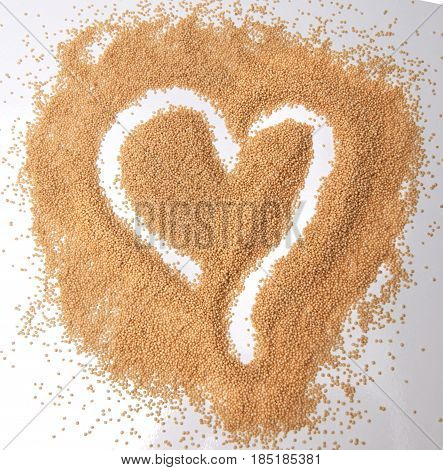 Amaranth seeds in a heart shape isolated on white background