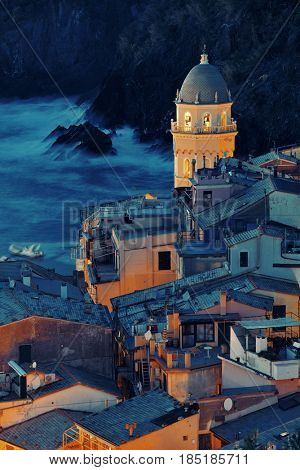 Landmark church bell tower and buildings at night in Vernazza, one of the five villages in Cinque Terre, Italy.