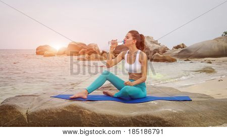 Fitness woman drink water after doing sport exercises on beach outside at sunset. Bottle of water after workout. 4K