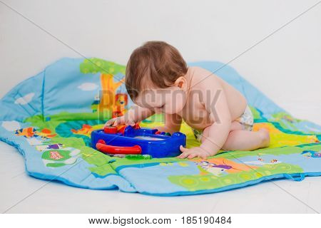 baby 6 months playing with educational toys in panties