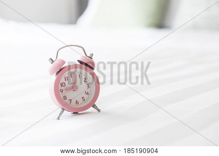 Alarm clock on the bed and time to wake up