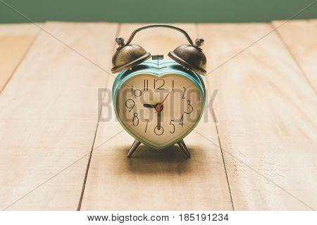 green heart alarm clock on the  table