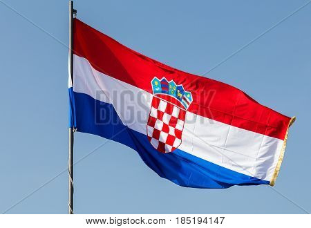 The national flag of Croatia flaps proudly above the old town captured under a clear blue sky.