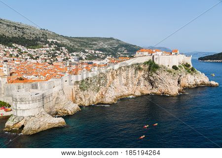 Colourful panorama of Dubrovnik's medieval city walls seen jutting out into the Adriatic Sea