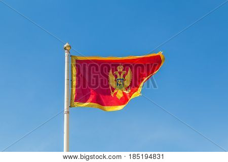 Montenegro flag pictured against a clear blue sky above the old Mediterranean port of Kotor.