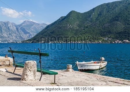 A bench seen facing out to the water in Perast seen at the foot of the rugged & rocky terrain of St Ilija on the Montenegro coastline.