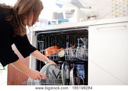 Woman opening the dishwasher in the kitchen