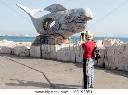 Acre Israel April 20 2017 : Young woman takes a picture of her daughter on a mobile phone that poses for her in a sculpture on the embankment of the Old City of Acre in Israel