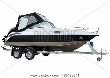 Modern boat with canvas top on a trailer for transportation.