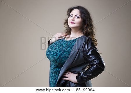 Plus size fashion model in casual clothes fat woman on beige studio background overweight female body
