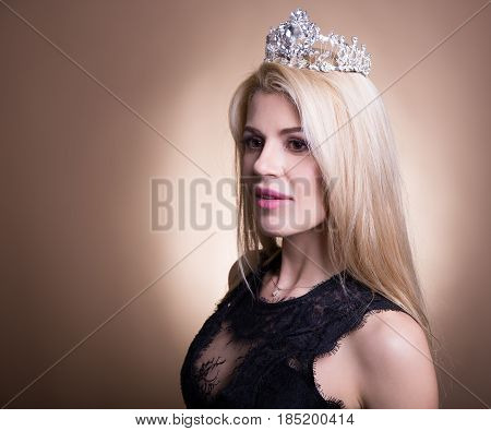Portrait Of Young Beautiful Blond Woman In Black Dress And Crown Over Beige