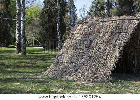 Nice view of straw tent. Straw tent on the green grass in the park.