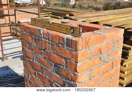 Building brick chimney in unfinished house construction roof. Bricklaying chimney.