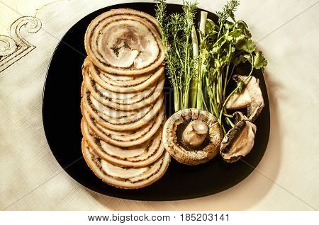 Sliced meatloaf with acute seasonings of smoked pork tenderloin on black plate