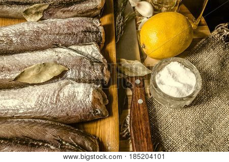 Frozen hake with spices and kitchen knife on chopping striped wooden board