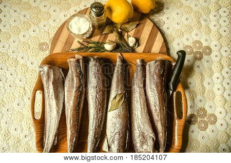 Frozen hake on tray with spices on the kitchen table covered with oilcloth tablecloth
