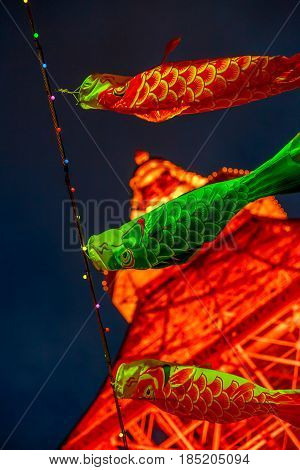 Tokyo, Japan - April 23, 2017: closeup of Koinobori a carp-shaped wind socks traditionally flown in Japan to celebrate Children's Day during Golden Week. Blurred Tokyo Tower by night on background.