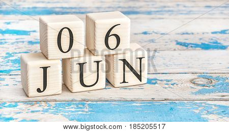 June 6th. Wooden cubes with date of 6 June on old blue wooden background.