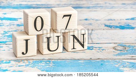 June 7th. Wooden cubes with date of 7 June on old blue wooden background.