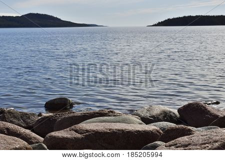 Shore with soft rounded granite stones in foreground and sea with islands in background picture from the North of Sweden.