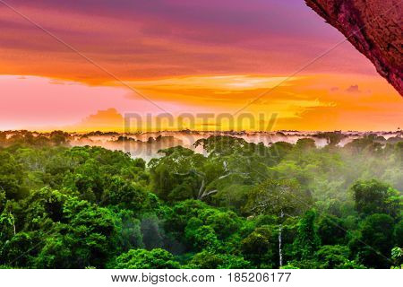 View onpPurple sunset over rainforest by Leticia in Colombia