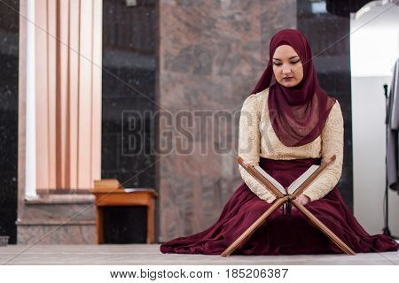 Young And Beautiful Girl Sitting Covered In Sumptuous Dress And Teaches The Quran Which Is Located O